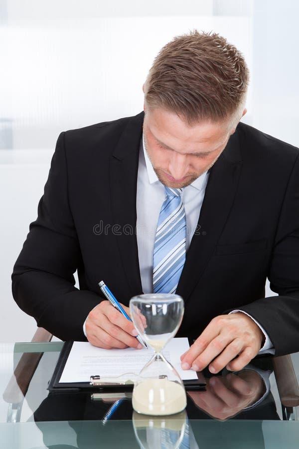 Homem de negócios sob a pressão de tempo imagem de stock