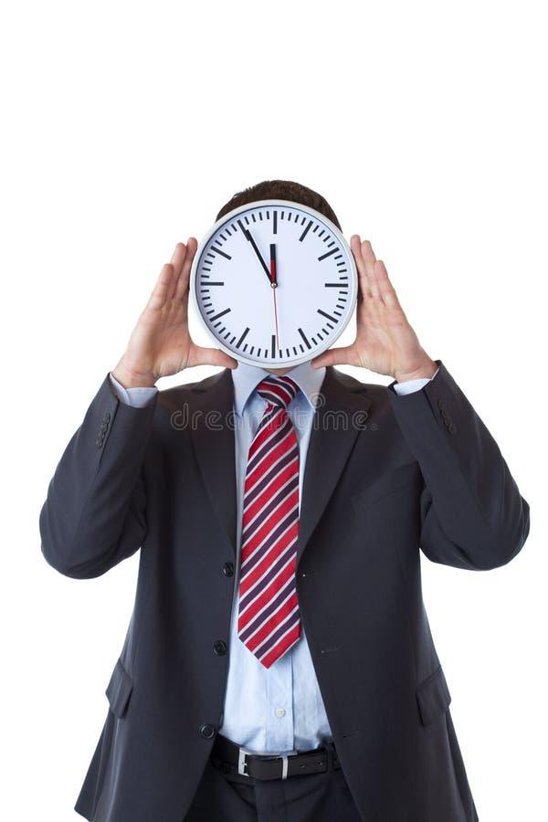 Homem de negócios sob a pressão de tempo atrás da face do relógio fotografia de stock royalty free