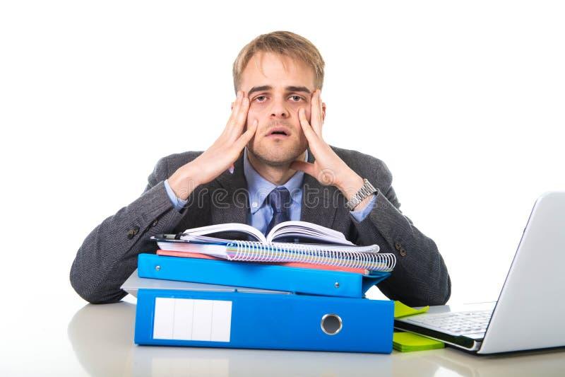 Homem de negócios sobrecarregado e oprimido dos jovens no esforço que inclina-se no dobrador do escritório esgotado e comprimido imagens de stock