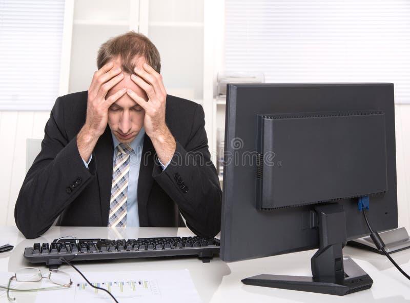 Homem de negócios sobrecarregado frustrado e forçado em seu escritório fotografia de stock