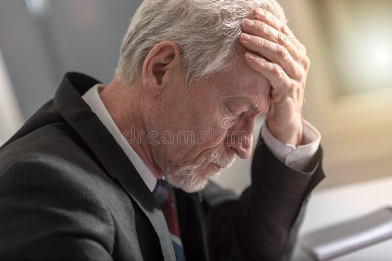 Homem de negócios sobrecarregado que tem a dor de cabeça imagem de stock