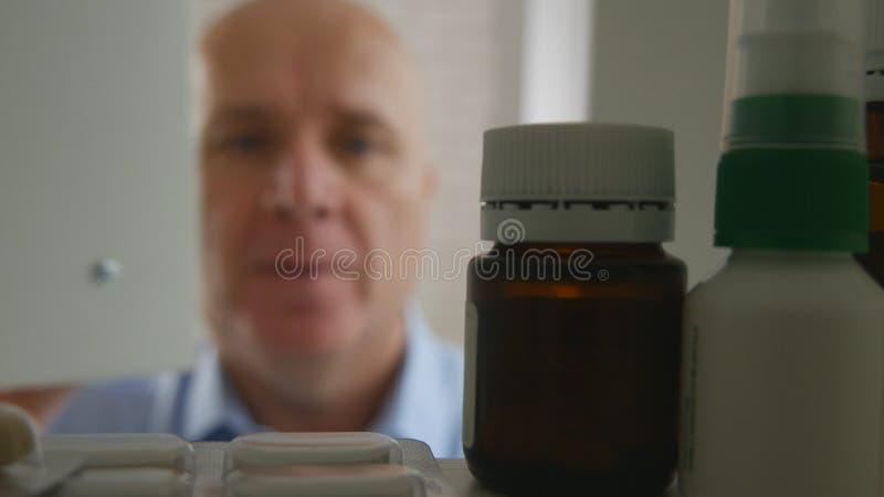 Homem de negócios de sofrimento que procura comprimidos médicos imagens de stock
