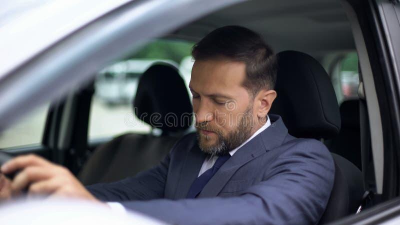 Homem de negócios sonolento no carro, manutenção da manhã, sentindo tonto, risco de acidente imagens de stock