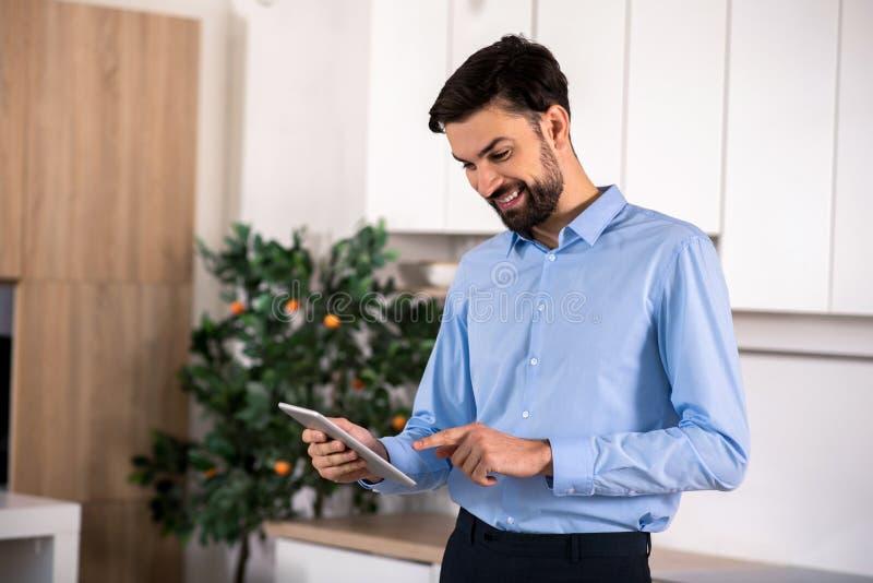 Homem de negócios de sorriso alegre que usa seu portátil foto de stock royalty free