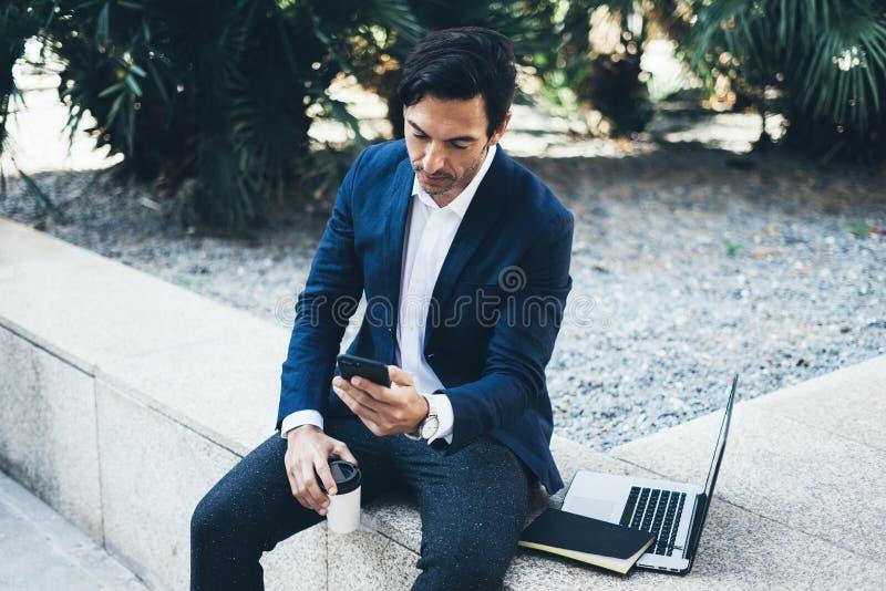 Homem de negócios de sorriso atrativo que usa o smartphone e o portátil contemporâneos ao tomar o resto durante o dia do trabalho foto de stock