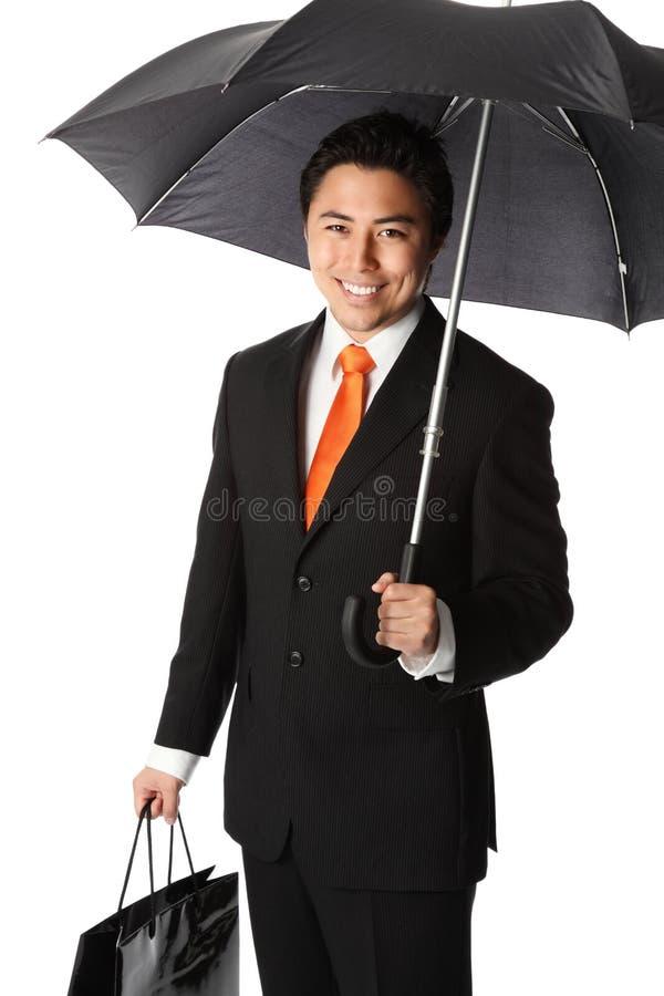 Homem de negócios de sorriso com guarda-chuva fotografia de stock royalty free