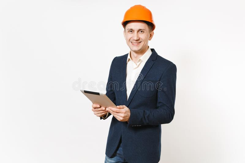 Homem de negócios de sorriso considerável novo no terno escuro, computador protetor do PC da tabuleta da terra arrendada do capac foto de stock