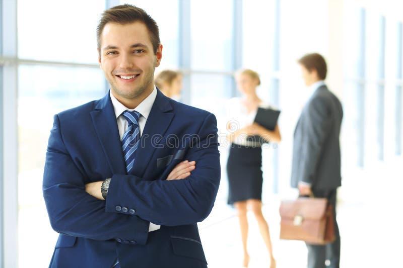 Homem de negócios de sorriso no escritório com os colegas no fundo foto de stock royalty free