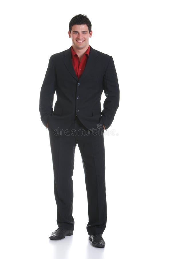 Homem de negócios de sorriso no levantamento preto do terno Está guardando as mãos em uns bolsos fotos de stock