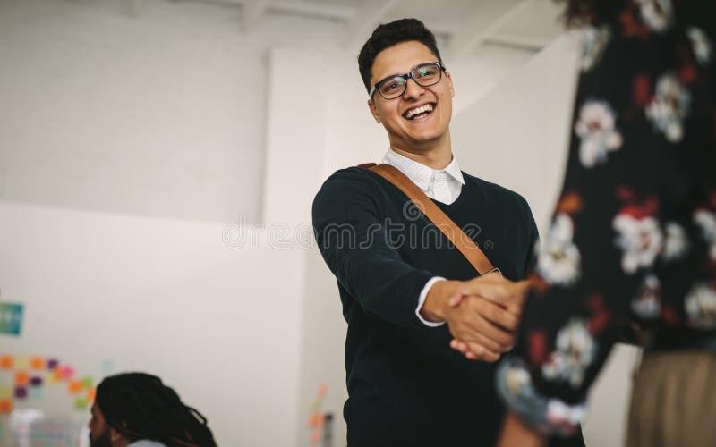 Homem de negócios de sorriso que cumprimenta um sócio comercial no trabalho fotos de stock