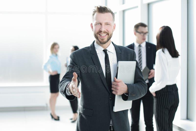 Homem de negócios de sorriso que dá sua mão para um aperto de mão fotografia de stock royalty free