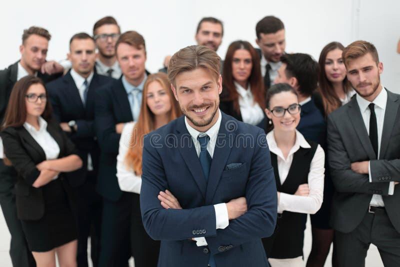 Homem de negócios de sorriso que está no fundo de sua equipe do negócio foto de stock