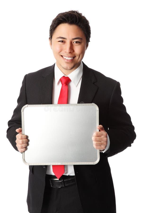 Homem de negócios de sorriso que mostra a placa vazia imagem de stock royalty free