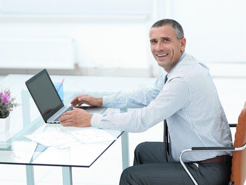 Homem de negócios de sorriso que senta-se na mesa e em olhar a câmera imagens de stock royalty free