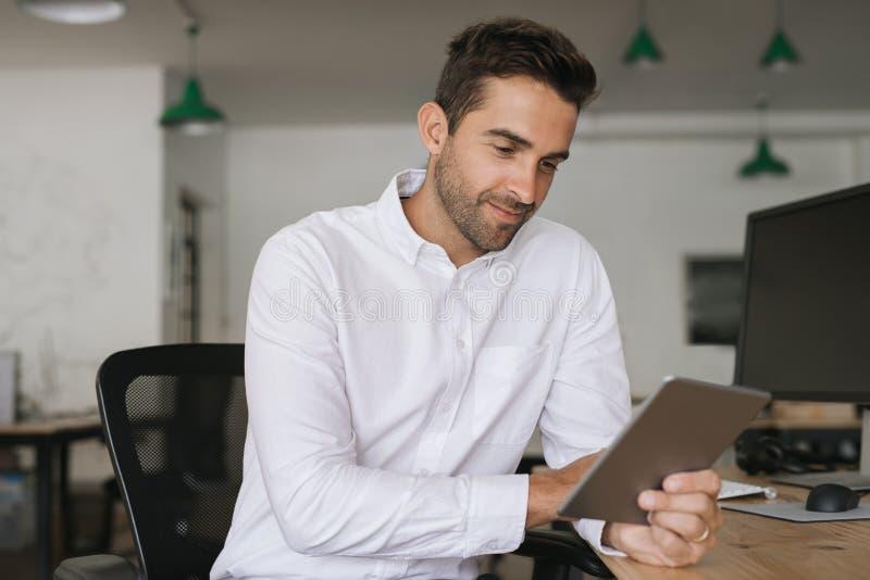 Homem de negócios de sorriso que trabalha em uma tabuleta em sua mesa de escritório fotos de stock