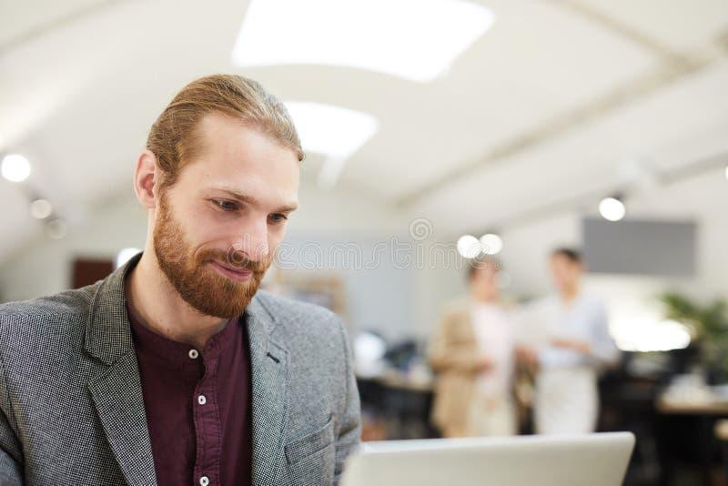 Homem de negócios de sorriso Working no escritório do espaço aberto imagem de stock royalty free