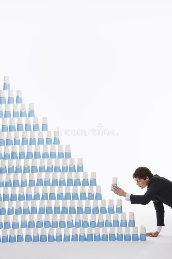 Homem de negócios Stacking Plastic Cups na pirâmide fotos de stock royalty free