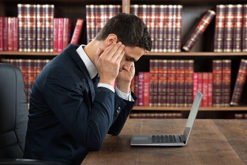 Homem de negócios Suffering From Headache ao usar o portátil imagens de stock royalty free