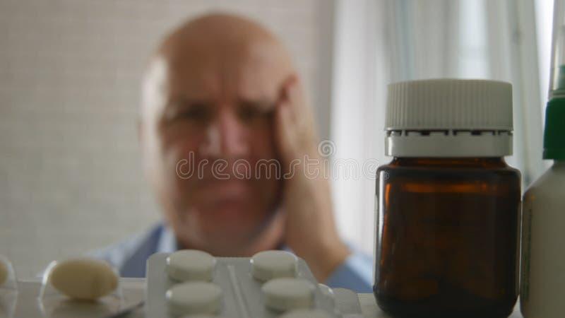 Homem de negócios Suffering um olhar grande da enxaqueca no armário de medicina para comprimidos imagens de stock royalty free