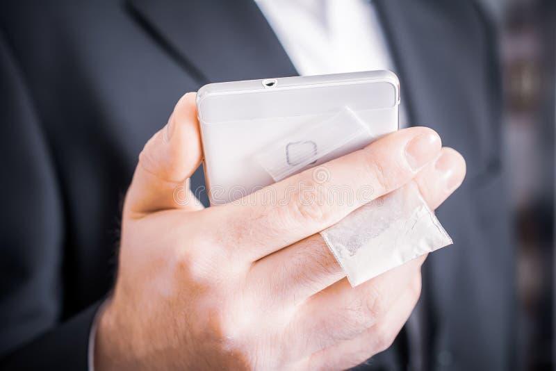 Homem de negócios In Suit Hiding um saco pequeno das drogas com pó branco atrás de seu telefone celular fotografia de stock royalty free