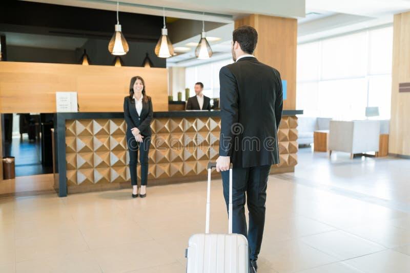 Homem de negócios With Suitcase Walking para o caixeiro In Lobby fotos de stock royalty free