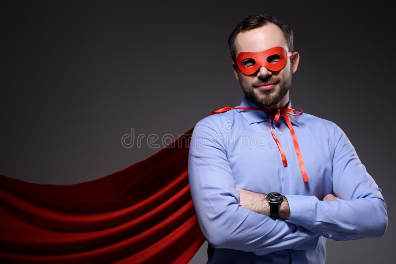 homem de negócios super de sorriso na máscara e cabo com braços cruzados fotos de stock