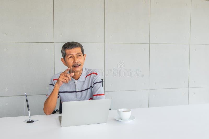 Homem de negócios superior asiático, pensando algo parte dianteira na mesa imagem de stock