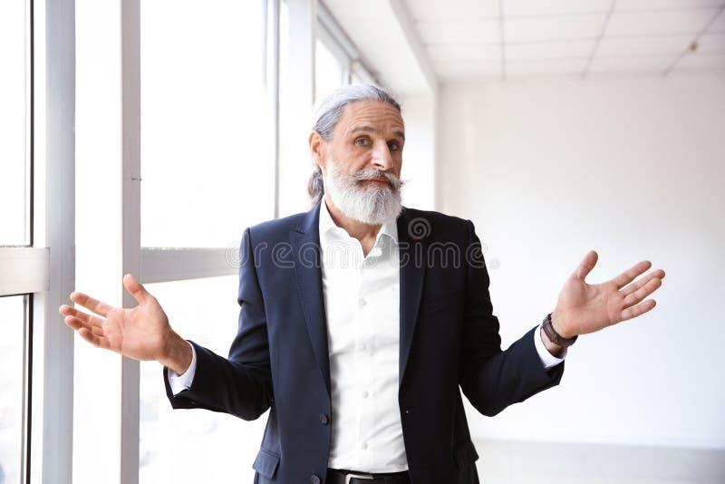 Homem de negócios superior emocional após ter feito o erro no escritório foto de stock
