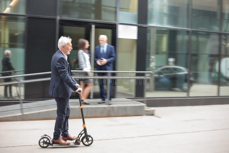 Homem de negócios superior feliz que comuta para trabalhar em um 'trotinette' do pontapé fotografia de stock royalty free