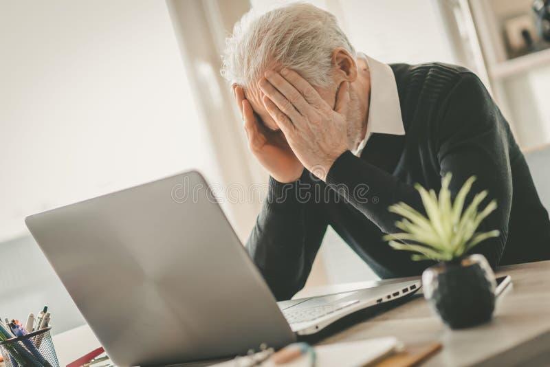 Homem de negócios superior forçado que senta-se no escritório imagens de stock