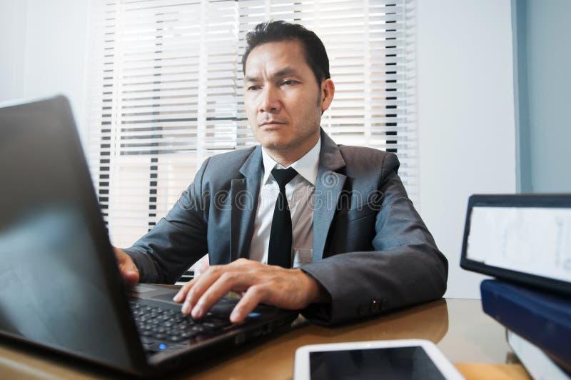 Homem de negócios superior no terno cinzento que senta e que usa o portátil no seu fotos de stock