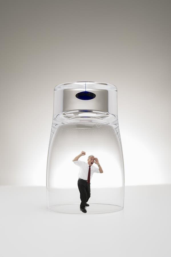 Homem de negócios superior prendido sob um vidro fotografia de stock royalty free