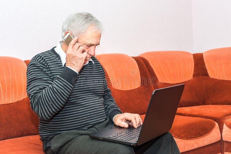 Homem de negócios superior que fala no telefone celular e que datilografa no portátil que senta-se no sofá foto de stock royalty free