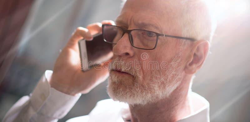 Homem de negócios superior que fala no telefone celular, efeito da luz fotos de stock royalty free