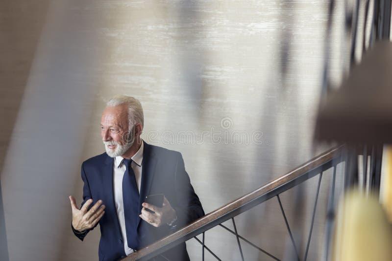 Homem de negócios superior que fala a um colega imagens de stock royalty free