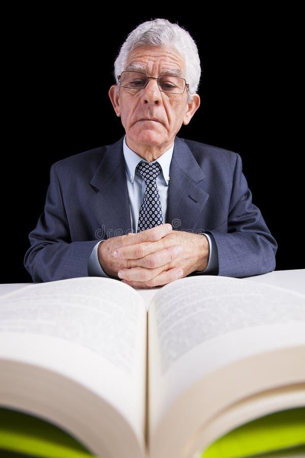 Homem de negócios superior que lê um livro fotografia de stock