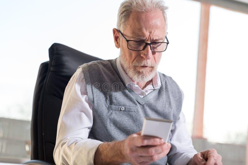 Homem de negócios superior que lê uma mensagem em seu telefone celular, luz dura fotografia de stock