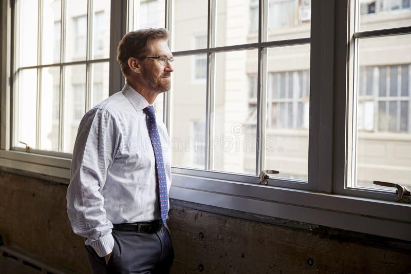 Homem de negócios superior que olha fora da janela, mãos em uns bolsos fotografia de stock royalty free