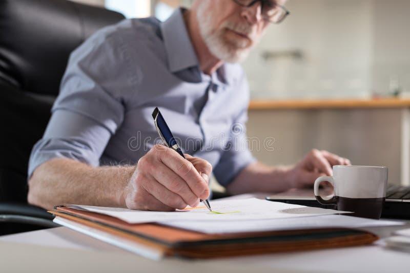 Homem de negócios superior que toma notas, luz dura fotografia de stock royalty free