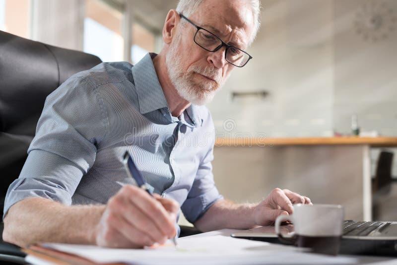 Homem de negócios superior que toma notas, luz dura, efeito da luz fotos de stock