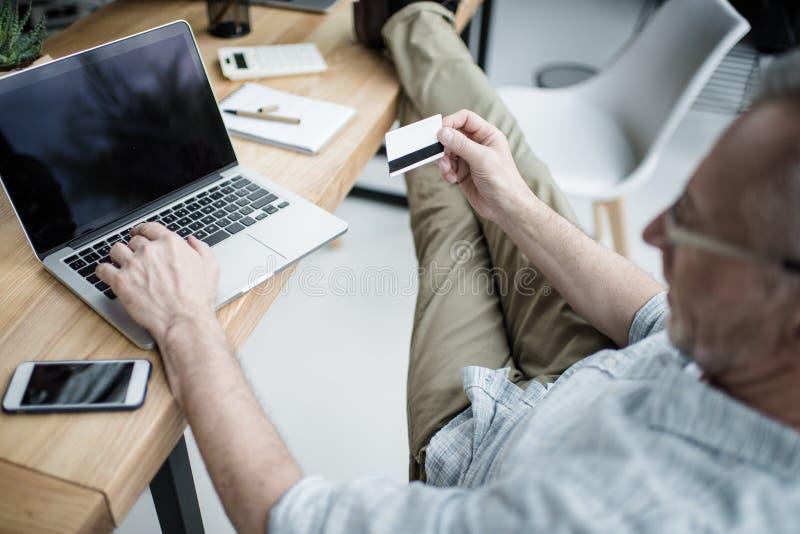 Homem de negócios superior que trabalha no portátil, fazendo a compra no Internet com cartão de crédito fotos de stock
