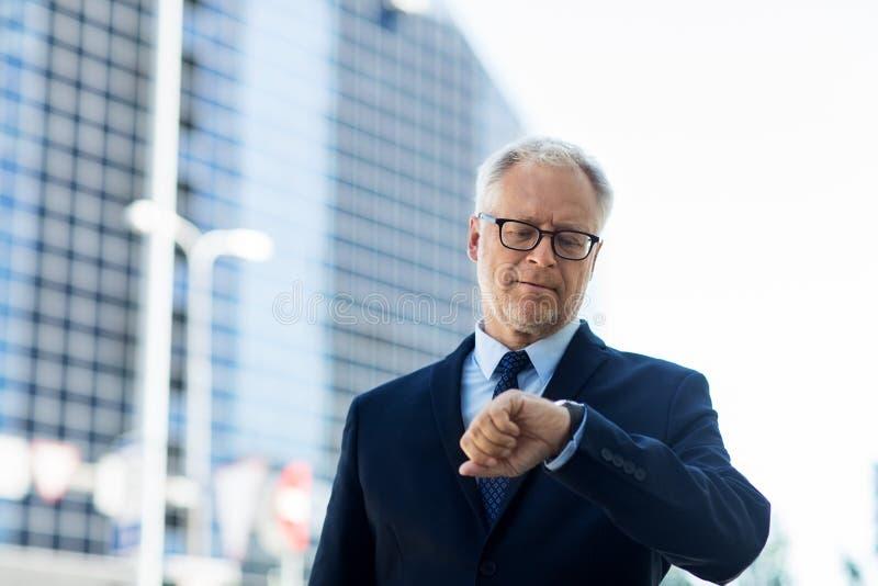 Homem de negócios superior que verifica o tempo em seu relógio de pulso fotografia de stock royalty free