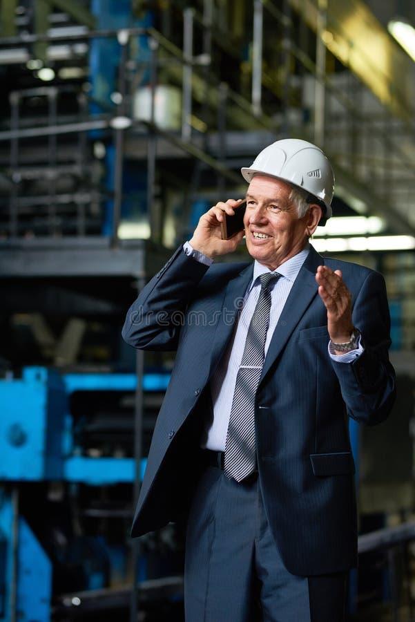 Homem de negócios superior Speaking pelo telefone na oficina da fábrica imagens de stock royalty free