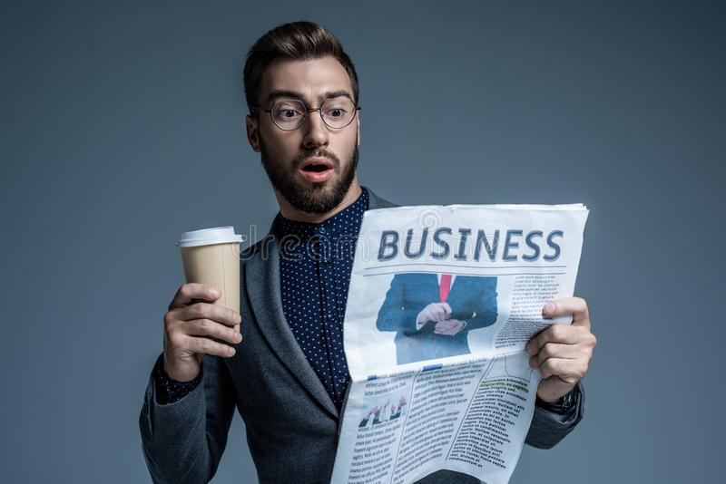 Homem de negócios surpreendido no terno e vidros que guardam um copo de papel e que leem o jornal de negócio fotografia de stock royalty free