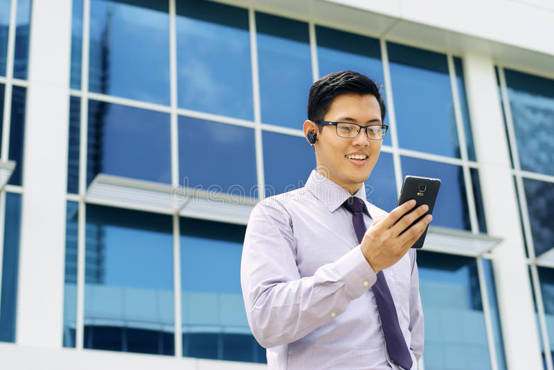Homem de negócios Talking Video Call no móbil com auriculares de Bluetooth foto de stock