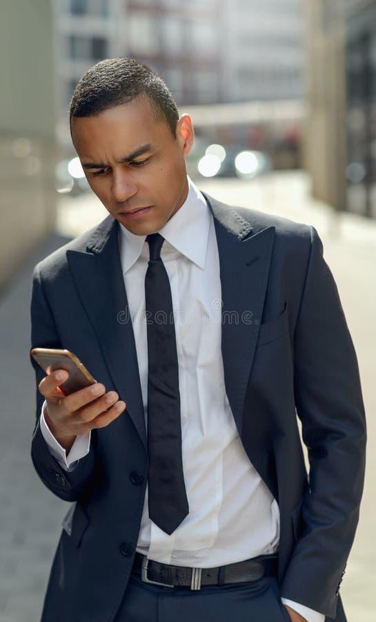 Homem de negócios Texting em seu telefone na rua fotografia de stock royalty free