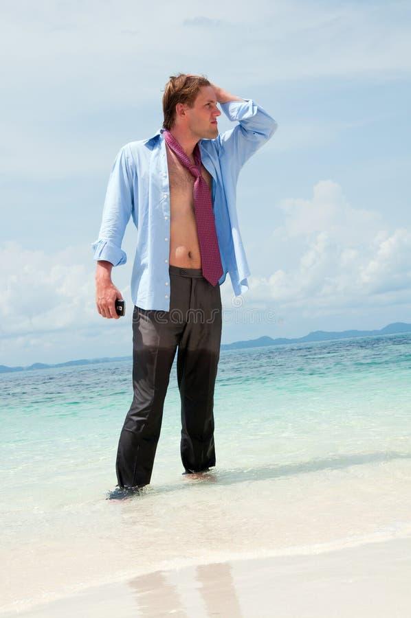 Homem de negócios Tired na praia foto de stock