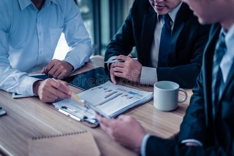Homem de negócios três que olha o gráfico no papel e a conversa sobre o plano de negócios, o mercado e o financeiro no futuro fotografia de stock royalty free
