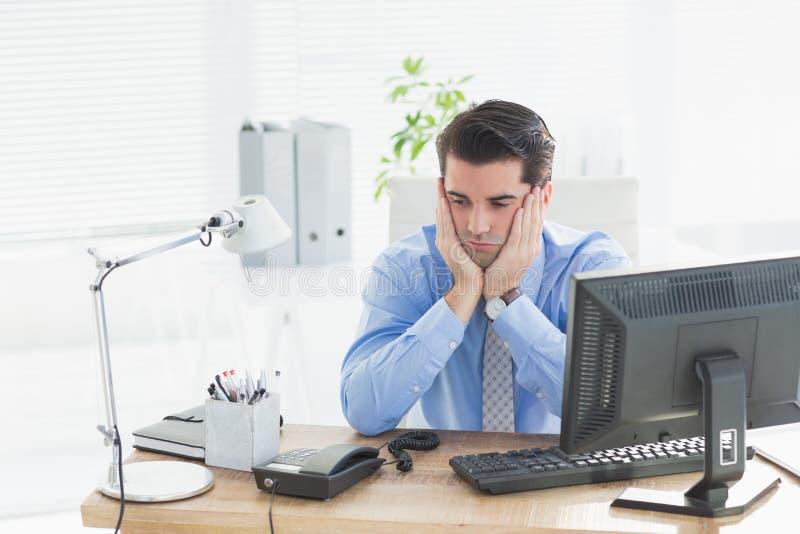 Homem de negócios triste que senta-se em sua mesa fotos de stock