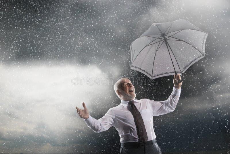 Homem de negócios With Umbrella Laughing na tempestade foto de stock